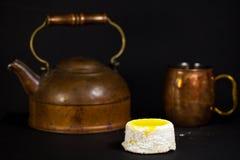 Lemon cake with powdered sugar on dark background with copper tea pot and mug. Custard lemon cake with powdered sugar on dark background with copper tea pot and Stock Photography