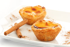 Custard Pies over a white plate with cinnamon sticks royalty free stock photo