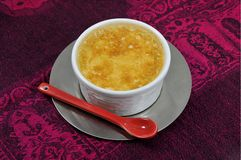 Custard with a red ceramic spoon Royalty Free Stock Photography