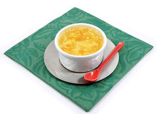 Custard with a red ceramic spoon on a green napkin Stock Image