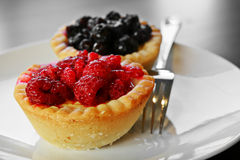 Custard tarts. Closeup of two tasty, delicious, pastry tarts with blueberries and raspberries Royalty Free Stock Photos