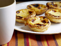 Custard tarts in a plate. With some softfocus  and a cup Stock Images