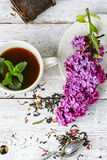 Custard tea and lilac. Custard flavored tea,spoon for welding and branch of blossoming lilac Royalty Free Stock Photography