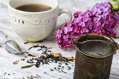 Custard tea and lilac. Custard flavored tea,spoon for welding and branch of blossoming lilac Royalty Free Stock Photo