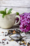 Custard tea and lilac. Custard flavored tea,spoon for welding and branch of blossoming lilac Stock Photo