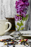 Custard tea and lilac. Custard flavored tea,spoon for welding and branch of blossoming lilac Stock Photography