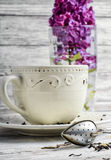 Custard tea and lilac. Custard flavored tea,spoon for welding and branch of blossoming lilac Stock Images