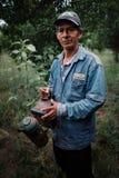 custode dell'ape e proprietario fiero dell'azienda agricola del caffè che preparano raccogliere uno del suo alveare con lo spruzz fotografia stock