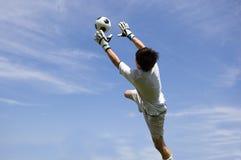 Custode di obiettivo di gioco del calcio di calcio che fa salvo Immagini Stock