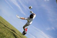 Custode di obiettivo di gioco del calcio di calcio che fa salvo Fotografia Stock