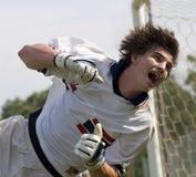 Custode di obiettivo di gioco del calcio di calcio che sforza per salvo Fotografia Stock