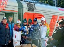 Custodi del fuoco e degli atleti Tatiana Navka e Roman Kostomarov al relè di torcia olimpico Fotografie Stock Libere da Diritti