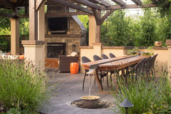 Custom Backyard Patio. An upscale backyard terrace featuring perennials and with a custom designed shelter and fireplace Royalty Free Stock Photo