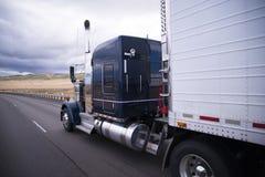 Custom big rig dark blue semi truck with reefer trailer Royalty Free Stock Photos