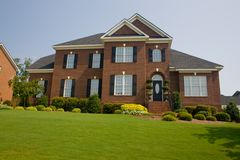 Custom brick home. Custom, upscale brick home with perfect green lawn Stock Images
