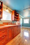 Custom build cherry kitchen with blue walls. Cherry cabinet kitchens and shiny floor Stock Photo