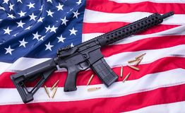 Custom built AR-15 carbine and bullets on American flag surface, background. Studio shot. royalty free stock photos