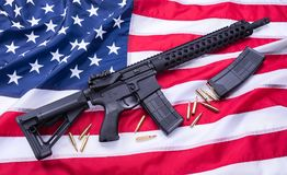 Custom built AR-15 carbine, bullets and a magazine on American flag surface, background. Studio shot. stock images