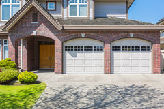 Custom built house. Double door garage. Custom built luxury house with nicely trimmed and designed front yard, lawn in a residential neighborhood, Canada stock photography
