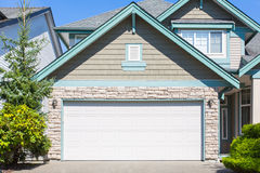 Custom built house. Garage door. Custom built luxury house with nicely trimmed and designed front yard, lawn in a residential neighborhood, Canada Royalty Free Stock Image