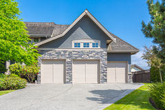 Custom built house. Garage door. Custom built luxury house with nicely trimmed and designed front yard, lawn in a residential neighborhood, Canada Stock Images