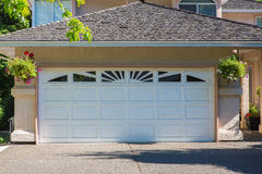 Custom built house. Garage door. Custom built luxury house with nicely trimmed and designed front yard, lawn in a residential neighborhood, Canada Royalty Free Stock Images