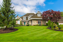 Custom built house. Custom built luxury house with nicely trimmed and designed front yard, lawn in a residential neighborhood, Canada stock photography