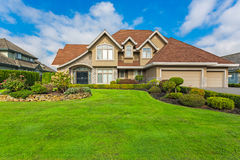 Custom built house. Custom built luxury house with nicely trimmed and designed front yard, lawn in a residential neighborhood, Canada Royalty Free Stock Images