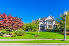 Custom built house. Custom built luxury house with nicely trimmed and designed front yard, lawn in a residential neighborhood, Canada royalty free stock photos