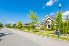 Custom built house. Custom built luxury house with nicely trimmed and designed front yard, lawn in a residential neighborhood, Canada Stock Images