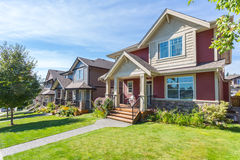 Custom built house. Row of houses. Custom built luxury house with nicely trimmed and designed front yard, lawn in a residential neighborhood, Canada stock photos