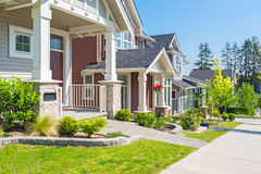 Custom built house. Row of houses in the spring. Custom built luxury house with nicely trimmed and designed front yard, lawn in a residential neighborhood Stock Photo