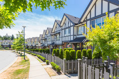 Custom built house. Row of townhouses. Custom built luxury house with nicely trimmed and designed front yard, lawn in a residential neighborhood, Canada Stock Photos