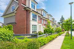 Custom built house. Townhouses in the spring. Custom built luxury house with nicely trimmed and designed front yard, lawn in a residential neighborhood, Canada Royalty Free Stock Photography