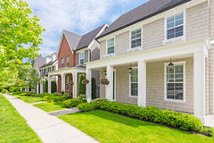 Custom built house. Townhouses in the spring. Custom built luxury house with nicely trimmed and designed front yard, lawn in a residential neighborhood, Canada stock photography