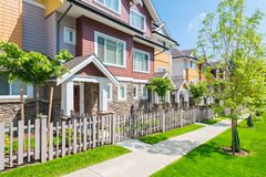 Custom built house. Townhouses in the spring. Custom built luxury house with nicely trimmed and designed front yard, lawn in a residential neighborhood, Canada Stock Images