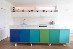 Custom designed kitchen island in open plan kitchen on industrial castor wheels, retro design painted in blue and green colours. Custom designed kitchen island stock images