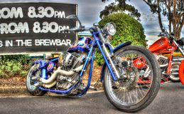 Custom designed motorcycle. Custom designed American style , blue and silver motorbike with extended forks on display at car and bike show in Melbourne stock photos