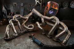 Custom exhaust manifold on welders work bench. In chop shop Royalty Free Stock Photo