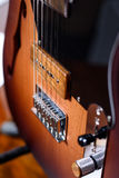 Custom Fender electric guitar with strings. Detail of brown electric guitar on a stand with strings Royalty Free Stock Photography