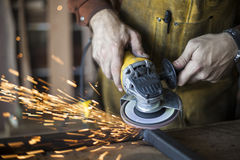 Custom furniture worker grinds weld seam on steel frame. Royalty Free Stock Photography