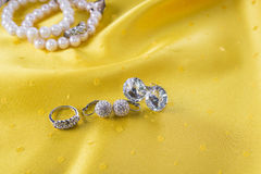 Custom jewelry like earings and ring on the yellow. Background Stock Photo