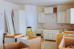 Custom kitchen cabinets in various stages of installation. Base for island in center Installation of kitchen cabinets Royalty Free Stock Photo