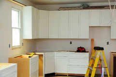 Custom kitchen cabinets in various stages of installation Stock Photo