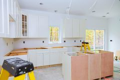 Custom kitchen cabinets in various stages of installation base for island in center Stock Photography