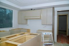 Custom kitchen cabinets in various stages of installation base for island in center. Installation of kitchen cabinets royalty free stock image
