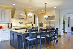Custom Luxury Kitchen. Kitchen from angle showing center island, stove (in background) and hallway Royalty Free Stock Images