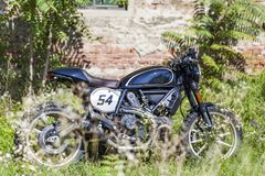 Custom made scrambler style cafe racer parking in the meadow near an old house royalty free stock images