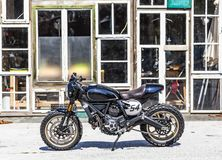 Custom made scrambler style cafe racer with standing in front of. Cool custom made scrambler style cafe racer with standing in front of a glass house stock photo