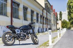 Custom made scrambler style cafe racer standing on road royalty free stock photos